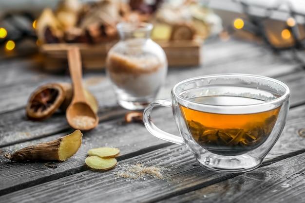 Bodegón con transparente taza de té sobre fondo de madera