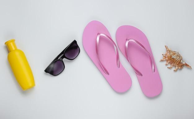 Bodegón de verano. accesorios de playa. chanclas de playa de moda rosa, botella de bloqueador solar, gafas de sol, concha sobre papel blanco.