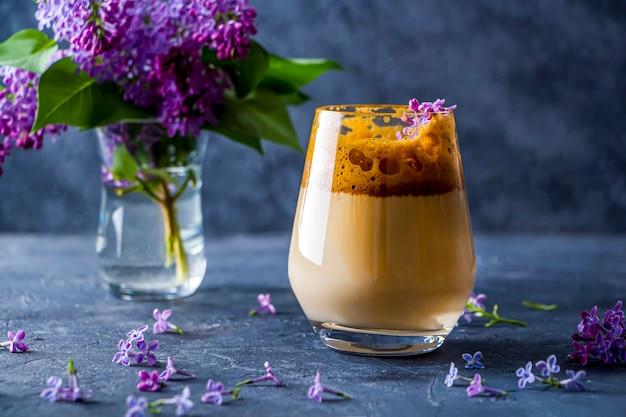 Bodegón de verano con café dalgona en vaso alto y flores lilas