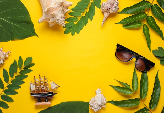 Bodegón de viajes de estilo retro. cámara de cine, gafas de sol, conchas marinas, hojas verdes tropicales. accesorios de viajero sobre fondo amarillo.