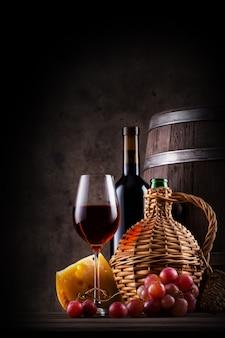 Bodegón de vino con barril y vino tinto.