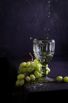 Bodegón con vino, uvas y copa de estilo antiguo.