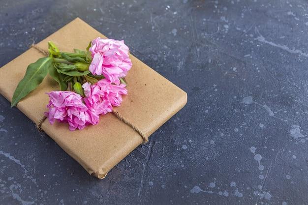 Bodegón vintage romántico con bonita caja de regalo envuelta con papel artesanal y decorada con flor rosa sobre fondo oscuro