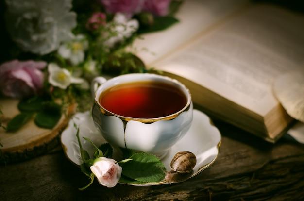 Bodegón vintage con una vieja taza de té de porcelana, rosa fresca, caracol y libro.