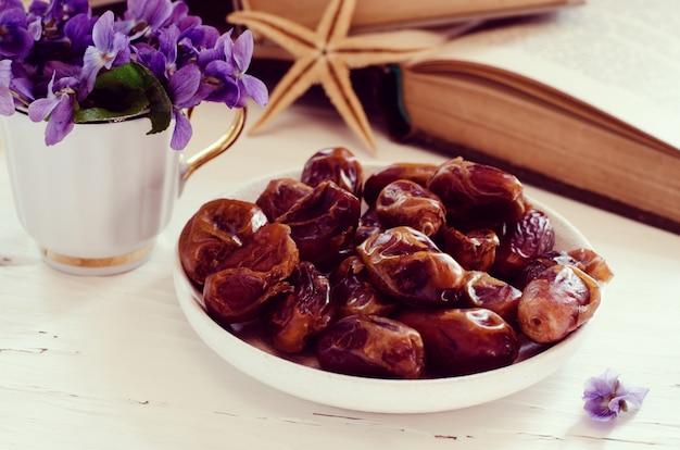 Bodegón con violeta en taza blanca, libros antiguos y frutas de fecha en un plato. floral romántico