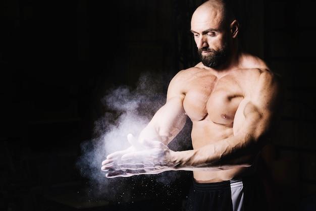 Bodybuilder frotando las manos con talco en polvo
