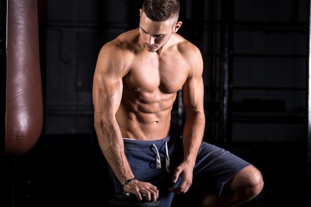 Bodybuilder joven con cuerpo perfecto