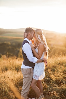 Boho mujer en vestido y accesorios de plumas en el cabello y hombre guapo en ropa elegante posando en el campo, abrazándose