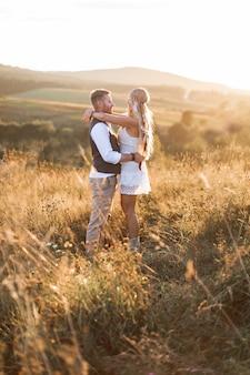 Boho ypsy mujer y hombre posando en el campo de verano