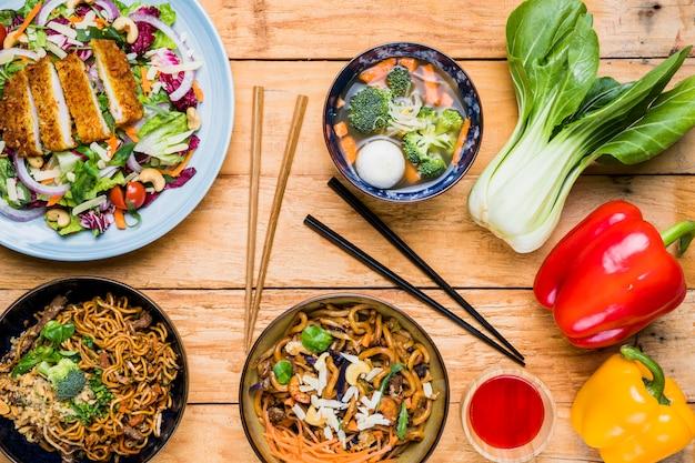 Bokchoy; pimientos y comida tradicional tailandesa en mesa contra fondo negro