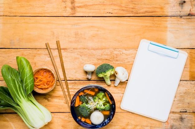 Bokchoy; zanahoria; sopa de bolas de pescado; palillos y portapapeles en blanco blanco sobre la mesa