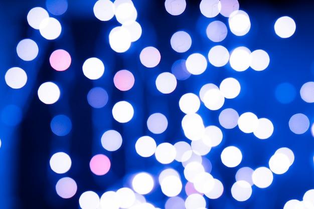 Bokeh de árbol de navidad azul y rosa sobre fondo negro de luces brillantes defocused
