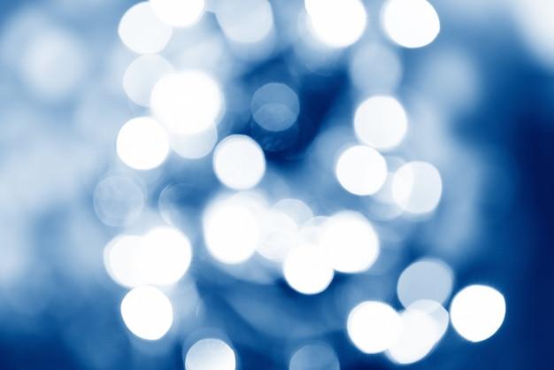 Bokeh azul borrosa y luces decoradas árbol de navidad sobre fondo negro para la celebración del festival de vacaciones
