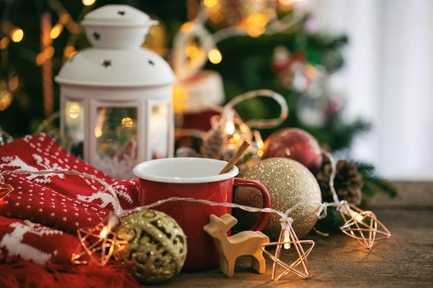 Bokeh de fondo de navidad decorado con rojo taza de chocolate, bufanda, linterna blanca, estrella intermitente.