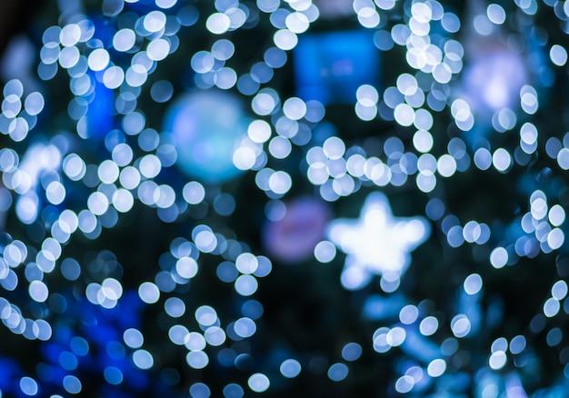 Bokeh ligero azul borroso extracto en el árbol de navidad en el fondo de la noche