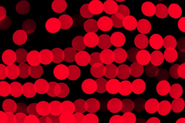Bokeh rojo abstracto desenfocado en fondo negro. desenfocada y borrosa muchas luces redondas
