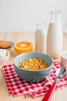 Bol de cereal con botellas de leche y naranja