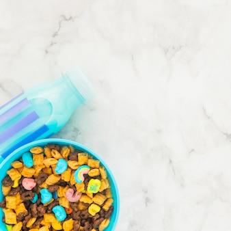 Bol con cereales y botella de leche azul.