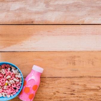 Bol con cereales y botella de leche rosa.