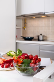 Bol de cristal con ají; pimiento y tomates cherry en la mesa en la cocina