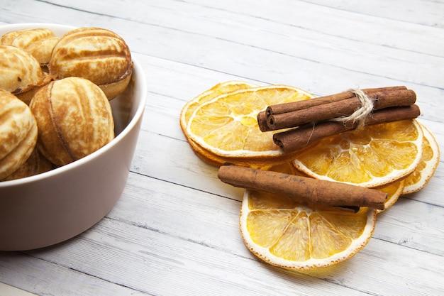 Bol con galletas - nueces y rodajas de naranja con canela sobre un fondo de madera claro