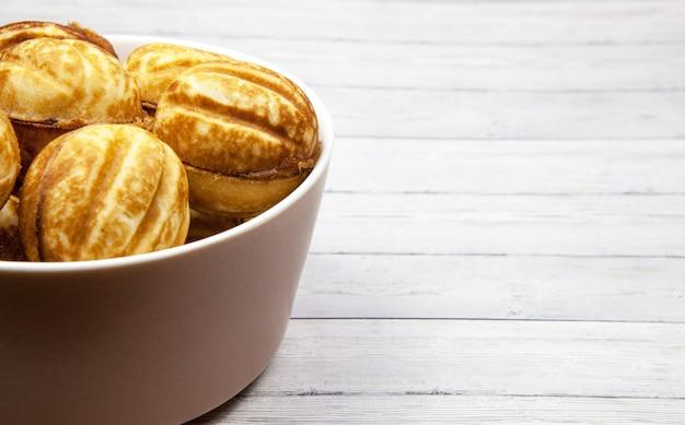 Bol con galletas - nueces sobre un fondo de madera