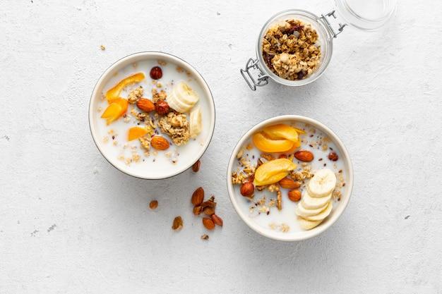 Bol de granola con frutas, nueces, leche y mantequilla de maní