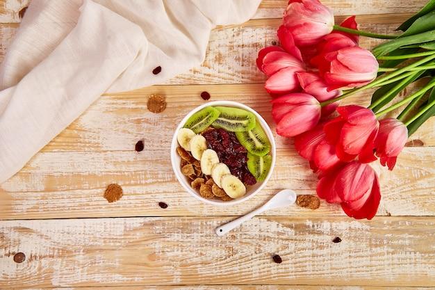 Bol con granola y ramo de flores de tulipán.