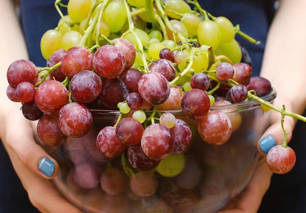 Bol de vidrio con uvas en manos femeninas.
