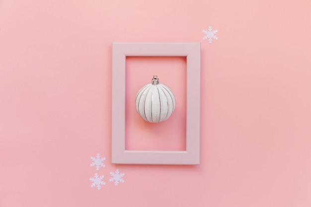 Bola de adorno de objetos de invierno en marco rosa aislado sobre fondo rosa pastel