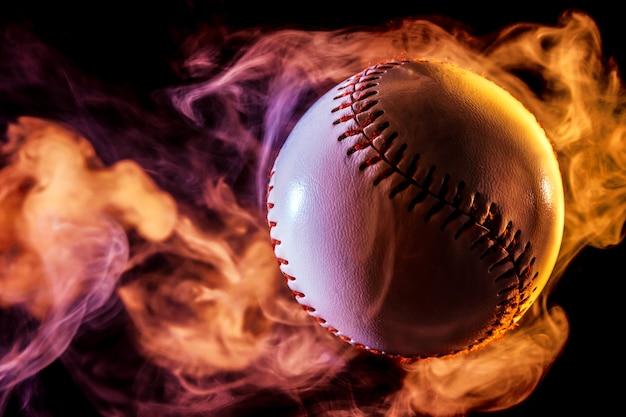Bola de béisbol blanca en humo rojo multicolor de un vape sobre un fondo negro aislado
