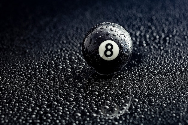 Bola de billar número ocho con gotas de agua sobre un negro
