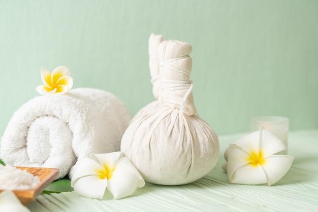 Bola de compresión de hierbas spa con vela y orquídea