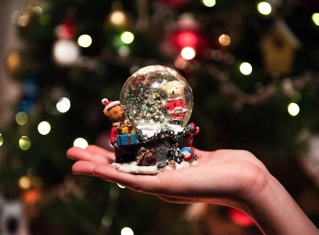 Bola de cristal de nieve en manos de la niña frente a bokeh