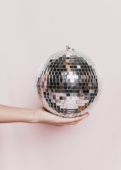 Bola de discoteca de mano en la fiesta de año nuevo
