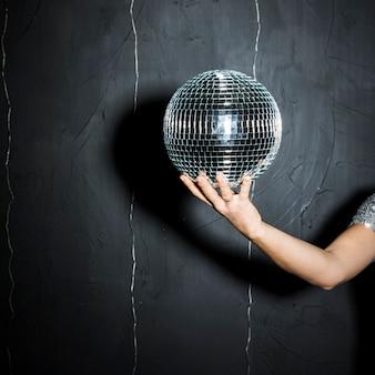 Bola de discoteca en mano de mujer.
