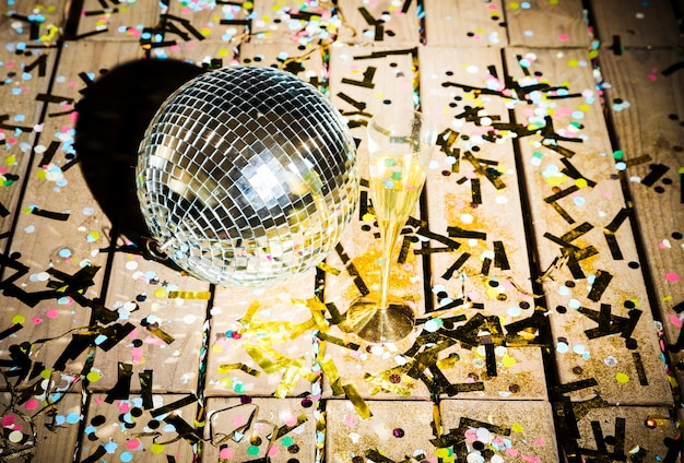 Bola de discoteca y vaso de bebida entre confeti.