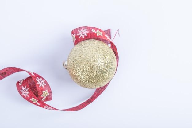 Una bola dorada brillante con cinta roja de navidad sobre el blanco.