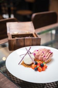 Bola de helado de vainilla y crumble de galleta con alce de chocolate y rebanada de fresa y mora. decorado con pequeñas flores y palos de taro púrpura.