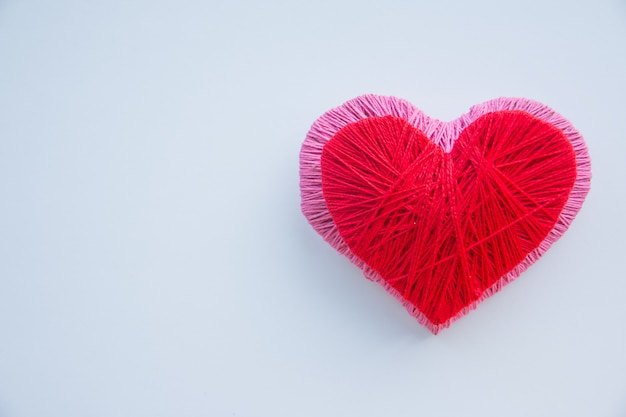 Bola de hilo colorido aislado. corazón rojo y rosa como un símbolo de amor. hobby