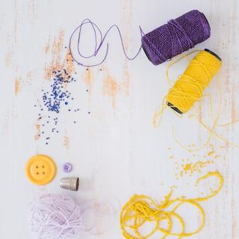 Bola de hilo morado y amarillo; botón con cuentas sobre fondo blanco con textura de madera
