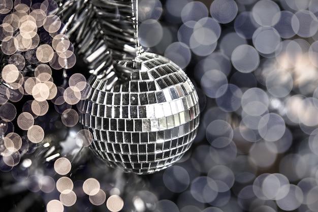 Bola de juguete de discoteca plateada brillante en el árbol de navidad con luces borrosas. concepto de vacaciones. de cerca.