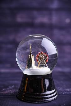 Bola mágica de navidad de globo de nieve congelada con copos de nieve voladores e iglesia y atracción.