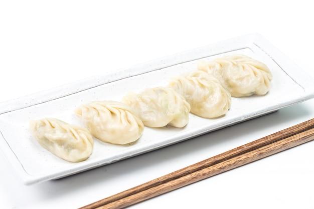 Bola de masa hervida hervida fresca en la placa. comida china con vapor caliente en el fondo.