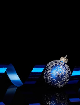 Bola de navidad azul con lazo sobre fondo negro reflectante brillante