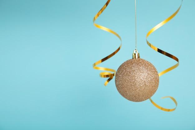 Bola de navidad dorada con cinta sobre fondo azul con espacio de copia. año nuevo 2022. vista superior