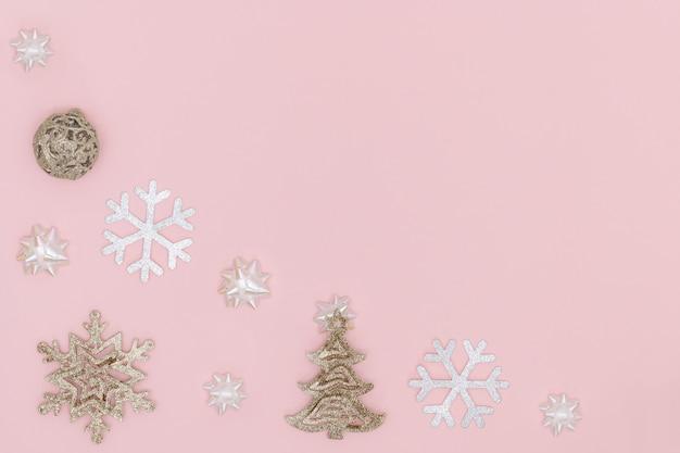 Bola de navidad dorada, copo de nieve, árbol de navidad, arcos de regalo sobre fondo rosa pastel