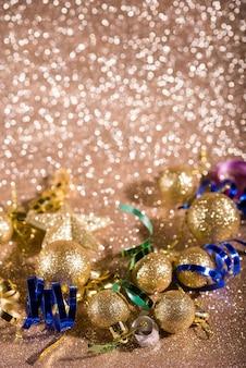 Bola de navidad dorada y decoración en luces borrosas