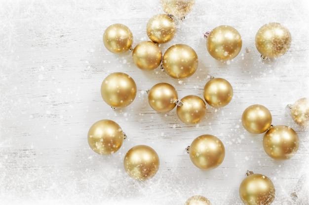 Bola de navidad dorada decorada en madera blanca con copos de nieve.