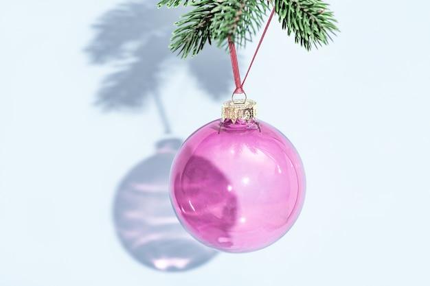 Bola de navidad redonda transparente púrpura colgando de la rama de pino